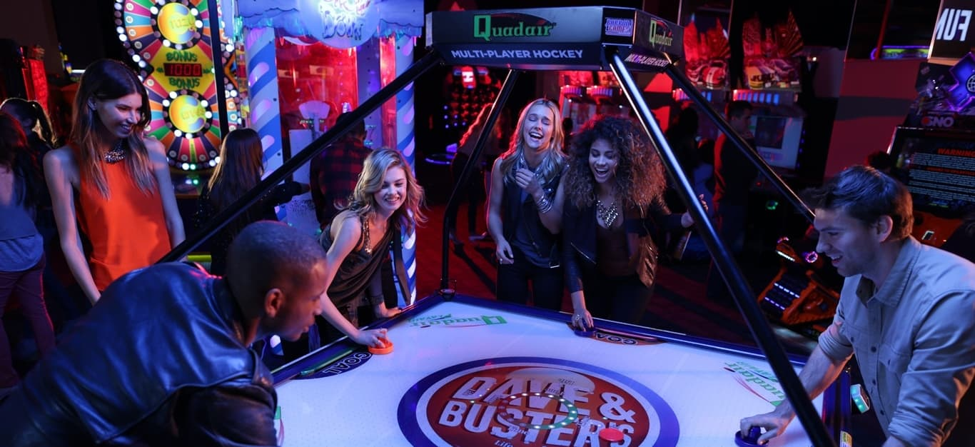 Group Playing Air Hockey in the Midway
